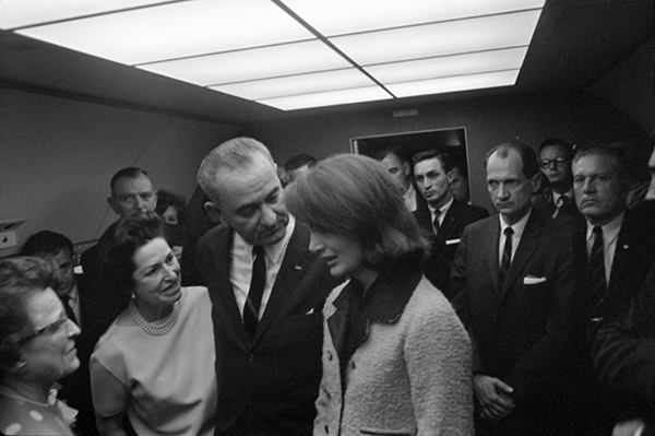 The swearing in of Johnson on Air Force One on November 22, 1963. L-R: Judge Sarah T. Hughes, Jack Valenti, Congressman Albert Thomas (behind Mrs. Johnson), Lady Bird Johnson, President Lyndon B. Johnson, Jacqueline Kennedy, Lem Johns, Congressman Jack Brooks, Bill Moyers (in the back), Dr. Burkley Credit: Cecil Stoughton