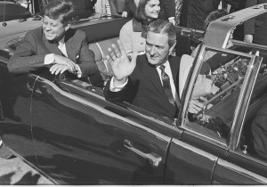 JFK, Jackie, and Governor Connally wave to the crowd as they pull out of Love Field to begin the motorcade.