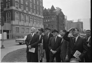 Members of the Warren Commission standing in Dealey Plaza at the corner of Elm and Houston streets, looking up at the sixth floor southeast corner window of the Texas School Book Depository building. Warren Commission members and staff include (left to right): Allen Dulles, unidentified, John Sherman Cooper, John McCloy, assistant counsel David Belin, Texas attorney general Waggoner Carr, and unidentified. Credit: Bill Winfrey Collection, The Dallas Morning News/The Sixth Floor Museum at Dealey Plaza
