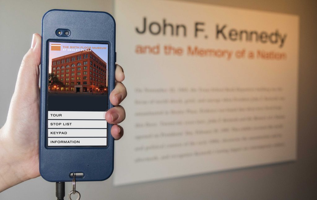 The Museum's audio guide, a personal handheld audio player, is held up in front of a sign which reads John F. Kennedy and the Memory of a Nation.