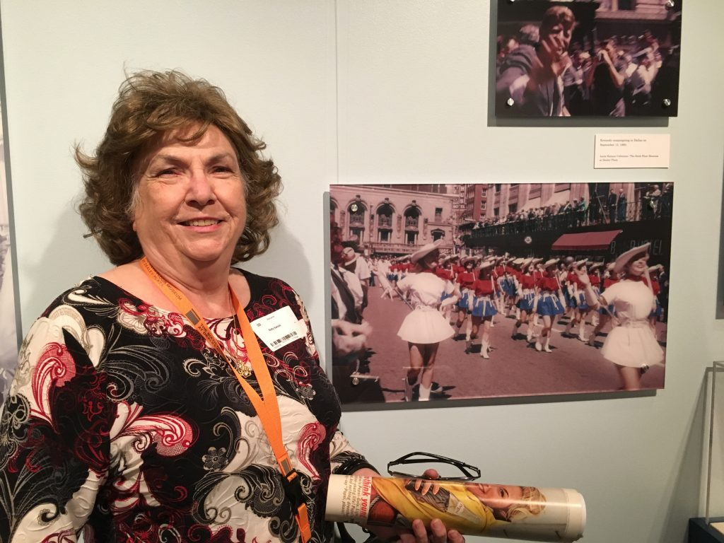 "Betty Barton in front of a photograph showing the Kilgore Rangerettes marching in the campaign parade for Sen. Kennedy on September 13, 1960. The photograph is from the Anita Hansen Collection and on display in the ""A Time for Greatness"" exhibition."