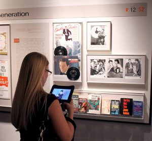 "A female guest with blonde hair stands in front of the ""A New Generation"" panel. She is holding an iPad on which she is watching a video of a sign language interpreter translating the museum's audio guide using American Sign Language."