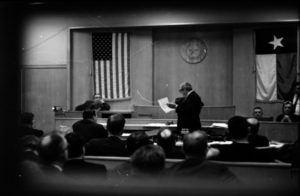 This photograph, taken through the window of the courtroom door, shows defense attorney Melvin Belli questioning PR executive Sam Bloom on the witness stand. The Dallas Morning News Collection/The Sixth Floor Museum at Dealey Plaza Donated by The Dallas Morning News in the interest of preserving history