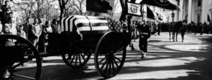 A horse-drawn caisson transports President Kennedy's flag-draped casket to St. Matthew's Cathedral.