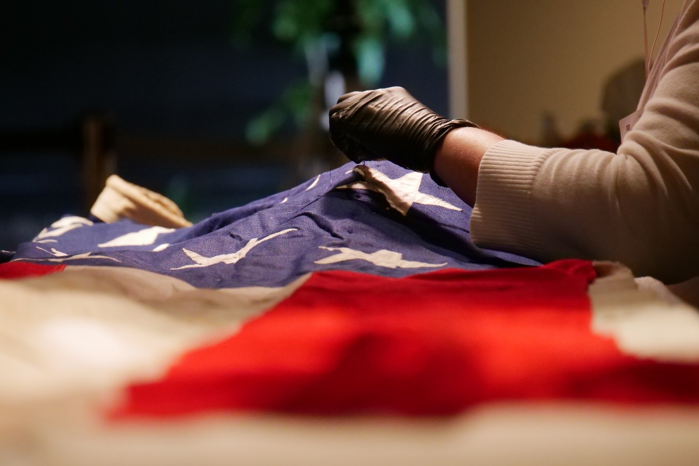 A textiles conservator carefully prepares the U.S. Senate wing flag for installation as part of the Mourning a President exhibit at The Sixth Floor Museum at Dealey Plaza